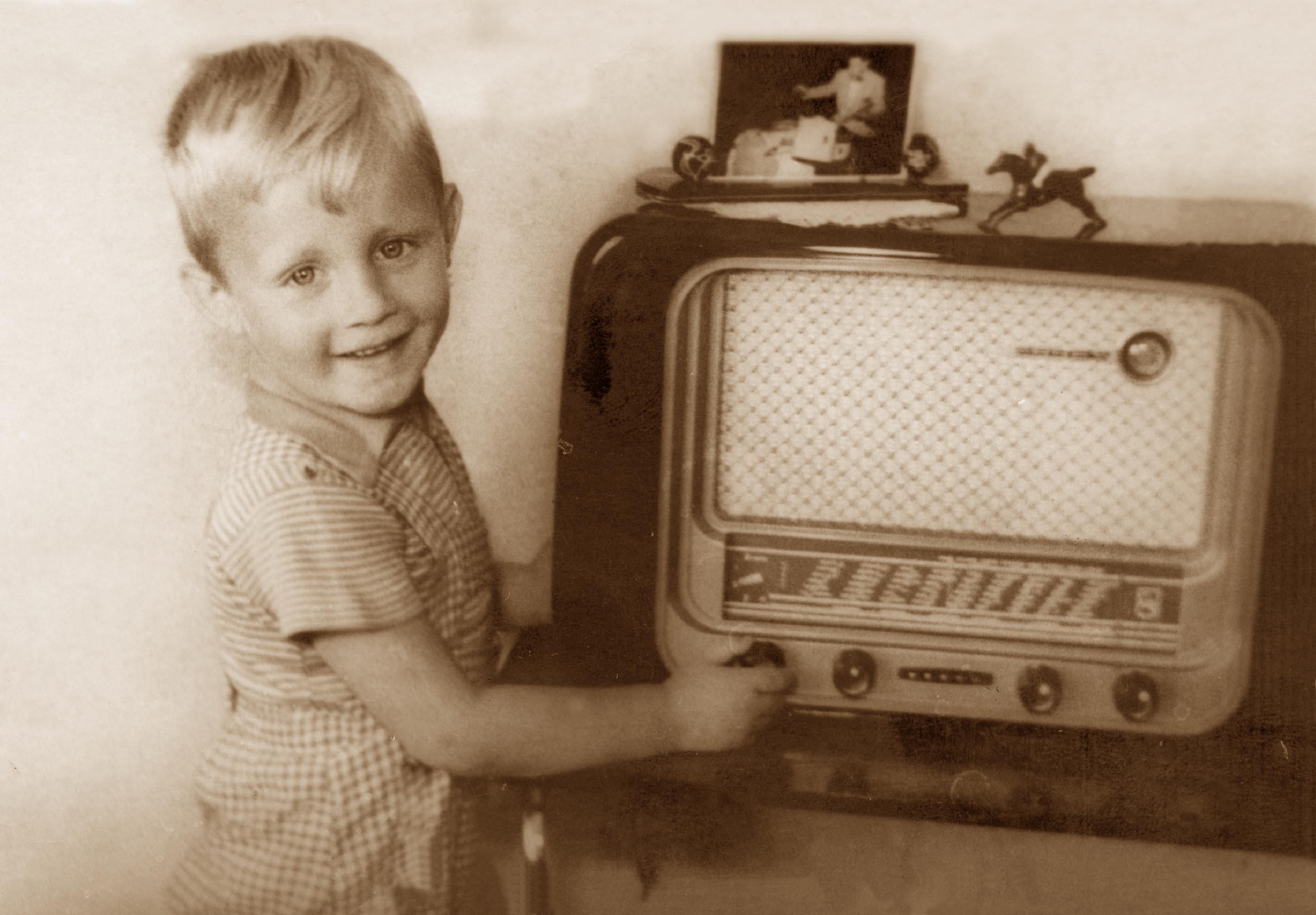 Peuter Bertusje aan de knoppen van een 50-tiger jaren buizen radio.